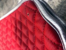 Pair of Slingshot insulated transmission tunnel pads in carbon fiber red and carbon fiber black close up