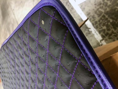 Pair of Slingshot insulated transmission tunnel pads in carbon fiber purple close up