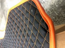 Pair of Slingshot insulated transmission tunnel pads in black and orange close up