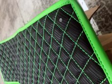 Pair of Slingshot insulated transmission tunnel pads in black and green close up
